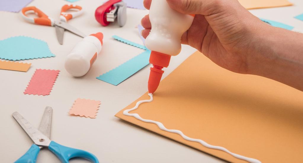 Taller infantil virtual (de 3 a 6 anys) - 085e2-human-hand-applying-white-glue-on-orange-paper-with-scissor-and-stapler_i646.jpg
