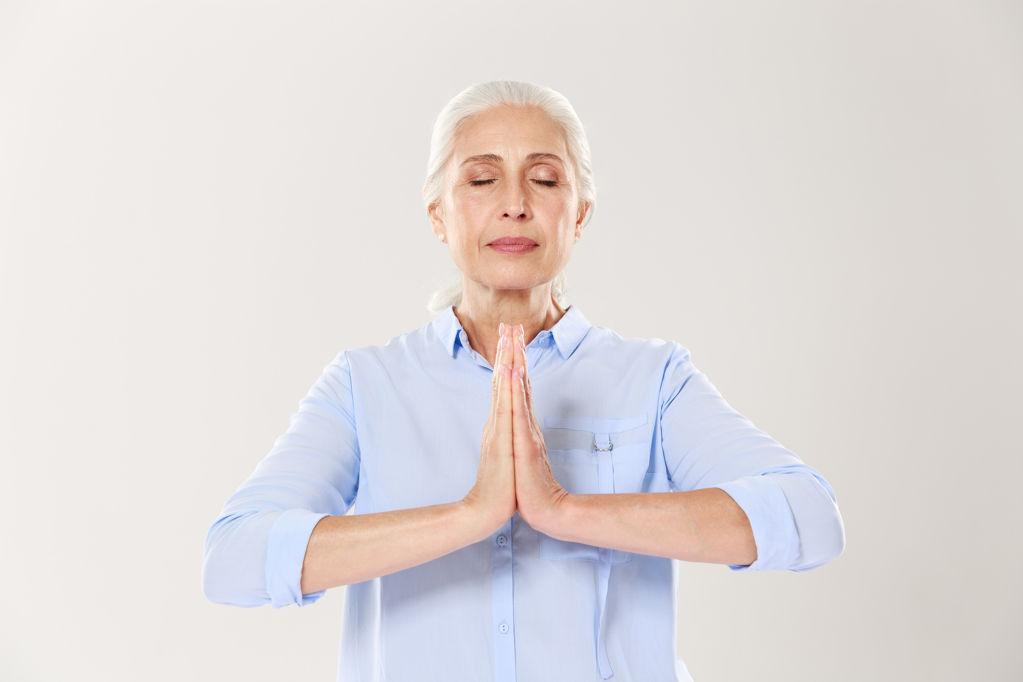 El dilluns 6 de setembre es reprèn el Ioga - 2081e-senior-woman-practising-yoga-holding-hands-in-namaste-and-keeping-her-eyes-closed.jpg